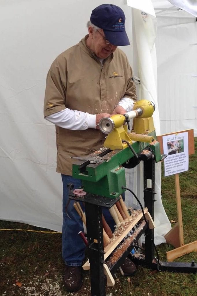 Woodlands resident Ervin Jones turns wood on a lathe at the Heritage Farm Museum